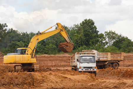 Industrial truck loader excavator moving earth and unloading into a dumper truck. Archivio Fotografico
