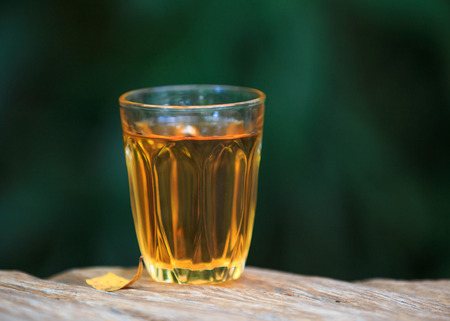 Yellow golden alcoholic drink in a brandy glass, on a wood table. photo