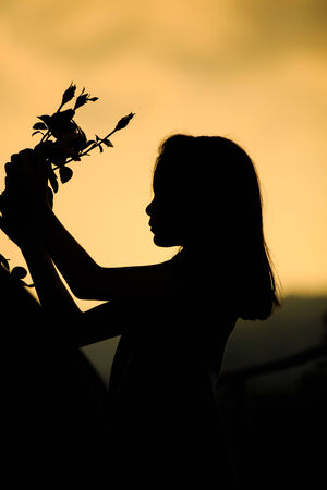 A young woman holding a rose at dawn in nature photo