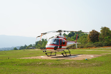 helipad: Helicopter parked at the helipad near forest. Stock Photo