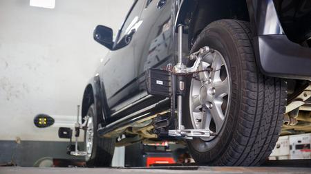 Auto auf dem Stand mit Sensoren auf Rädern für Räder Ausrichtung Sturzprüfung in der Werkstatt des Service-Station. Standard-Bild - 38740173
