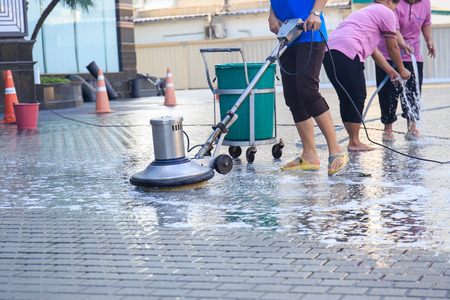 bioclean: Adult cleaner maid woman with mop and uniform cleaning corridor pass or hall floor of business building
