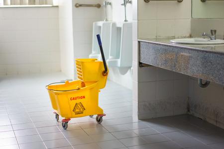 Mop bucket on wet floor in toilet.
