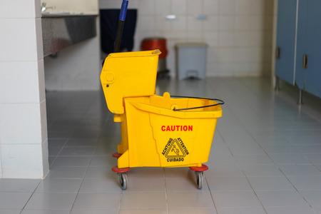 mopped: Mop bucket on wet floor in toilet.