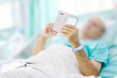 Mature male patient playing a mobile on bed in hospital.