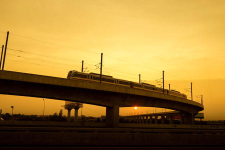 commuter train: Commuter train on elevated track at sunset