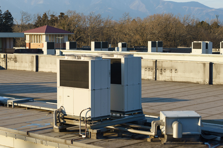 A row of air conditioning units on a rooftop.