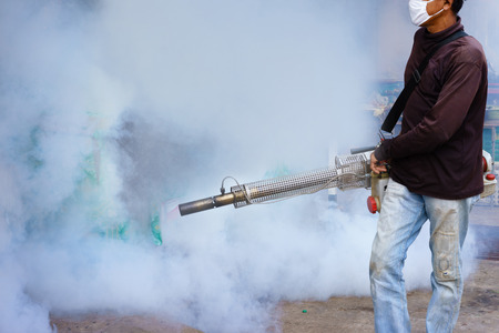 aedes: Worker fogging drain at residential area with insecticides to kill aedes mosquito. Stock Photo