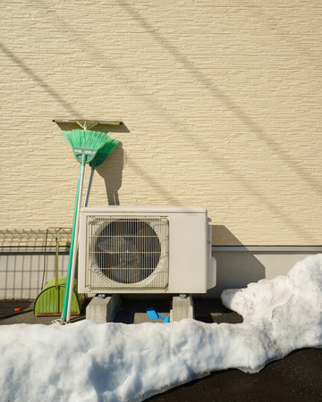 heat pump: Heat pump unit on the side of a home in winter