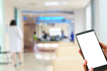 Man hand holding mobile smart phone and blurred figures of doctors and nurses in a hospital corridor. Stockfoto