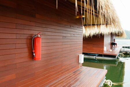 Fire extinguisher hanging outside floating hotel houses.