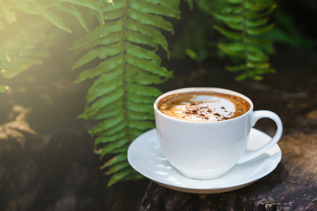 Cup of coffee cappuccino art on wood floor with green leave frame. Stock Photo