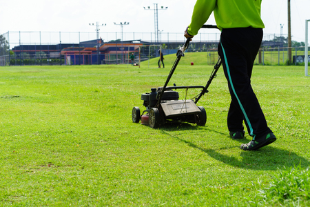 Man cutting the grass with lawn mower. Stock Photo
