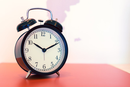 counting five: Vintage background with retro alarm clock on table.
