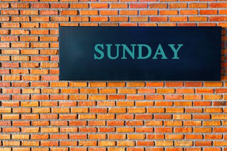 concrete block: SUNday letters on a black background with  brick wall. Stock Photo