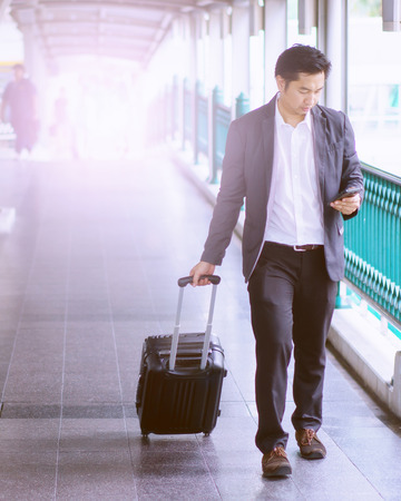 Businessman with trolley bag using mobile phone. Stock Photo