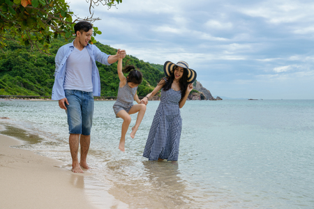 Happy family playing on the beach at the day time. Stock Photo