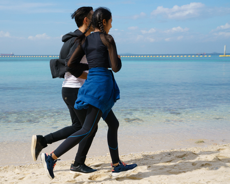 Couple jogging along the beach Stock Photo