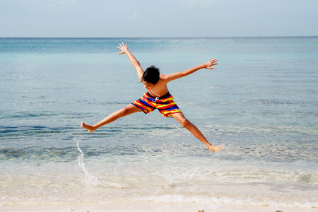 Young boy jumping on the beach. Stock Photo