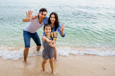Portrait of happy family, taking selfie on beach