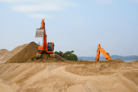 Excavator is preparing pile of sand for loading in truck on buil. Stock Photo