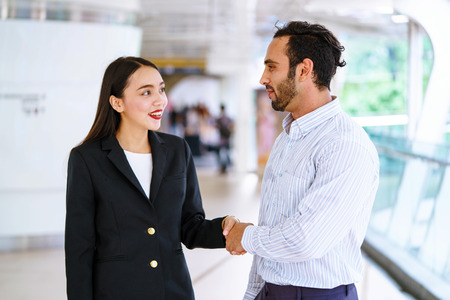 Two business people shaking hand to partner.