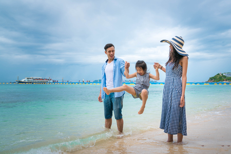 Family with kid playing on beach. Stock Photo