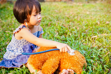 Little girl playing doctor with teddy bear outdoors. Stock Photo