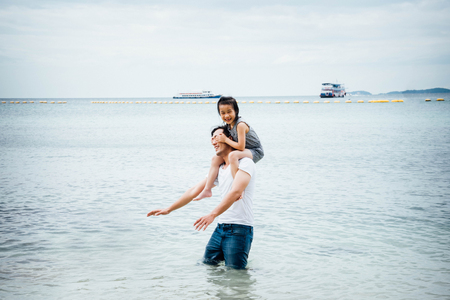 Father and daughter having fun on beach. Stockfoto