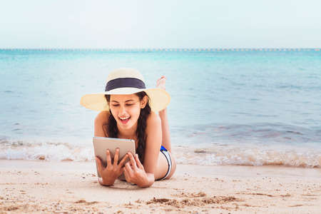 Young woman using tablet computer on the beach. Stock Photo