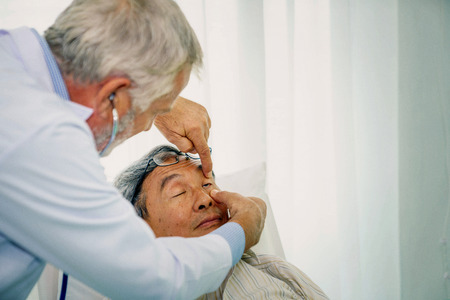 Senior doctor checking his patient eyes.