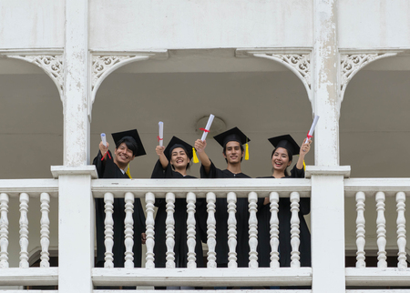 People students in the feeling of happy with the graduation gowns hold the cap. Stockfoto