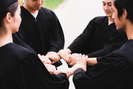 people with black gowns join hand in circle loop