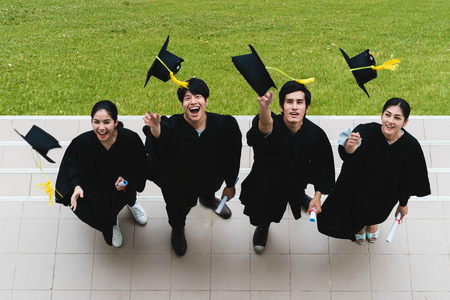 People students in the feeling of happy and graceful with the graduation gowns throw up the cap