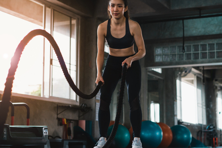 Fit young woman exercising with ropes at the gym.