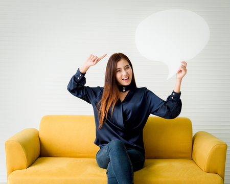 Beautiful woman holding a speech bubble on a yellow sofa. Фото со стока