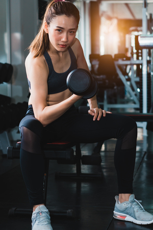 Young Beautiful woman exercising with weight in the gym. Stock Photo