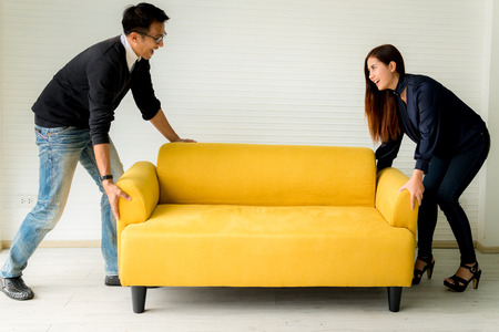 Couple lifting sofa in living room Stock Photo