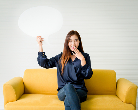 Beautiful woman holding a speech bubble on a yellow sofa. Stock Photo