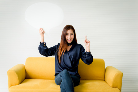 Beautiful woman holding a speech bubble on a yellow sofa.