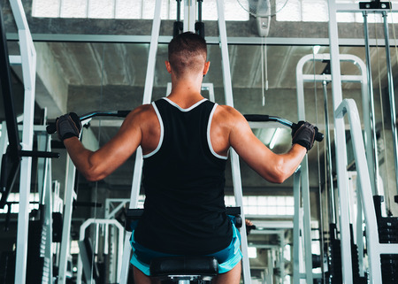 Man flexing muscles on cable machine in gym