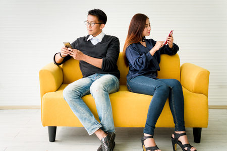 Relationship difficulties and people concept - couple with smartphones texting on yellow sofa at home