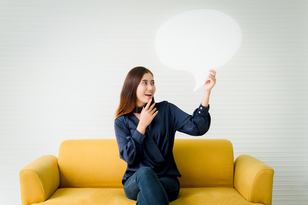Beautiful woman holding a speech bubble on a yellow sofa Stock Photo