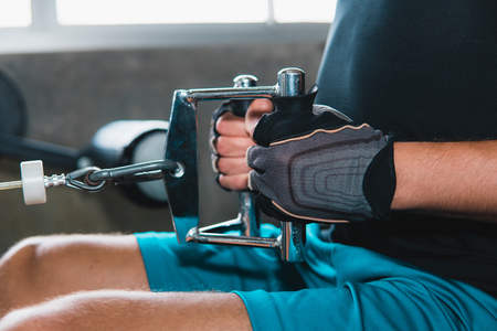 Close-up shot of sport man doing exercise on rowing machine at modern gym