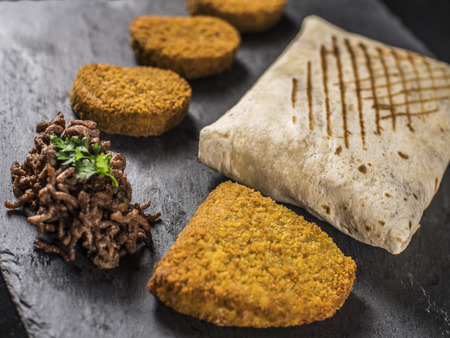 Close up on English Tacos with Nuggets, Blue Cord and Beef on slate Archivio Fotografico