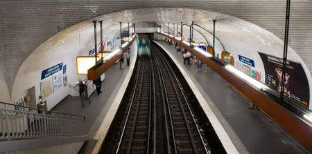 Underground train station in paris with train running