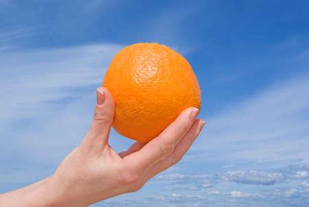 Main avec un orange contre le ciel.