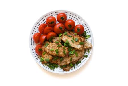 Fried viande avec des tomates sur une plaque.