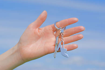 Hand with a key against the sky photo