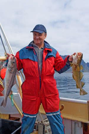 P�cheur avec des poissons sur le bateau pr�s de le �le Lofoten  Banque d'images